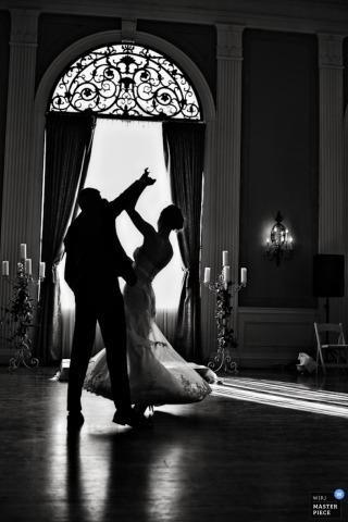 Fotografía de bodas de Denver de la novia y el novio como siluetas bailando delante de una ventana