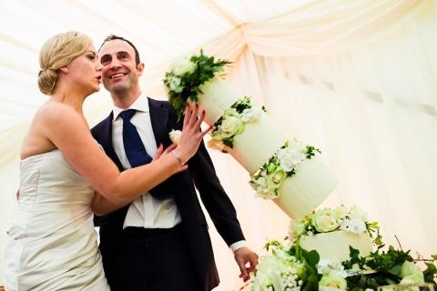 Foto de novia y novio en el Reino Unido de un pastel que se cae en la recepción de la boda