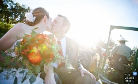 Fotografía de bodas en Denver de los novios besándose mientras son arrastrados detrás de un tractor