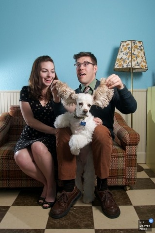 Engagement Portrait of a couple sitting on a small couch with their dog with large ears