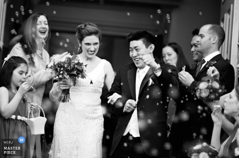 Bride and Groom exit the ceremony with guests celebrating with flying bubbles