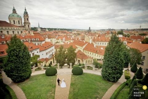 Fotografia ślubna Europy i Włoch przedstawiająca narzeczonych spacerujących w otoczeniu architektury.