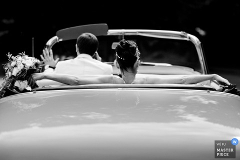 Lower Saxony groom and bride in a convertible car on wedding day