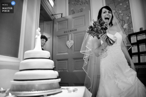 Hertfordshire Wedding Reportage Photographer - UK   Image contains: bride flowers happy expression cake dress reception