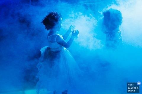 Lyon Wedding Photography | Image contains: kids girl dress play fog machine blue lights boy reception