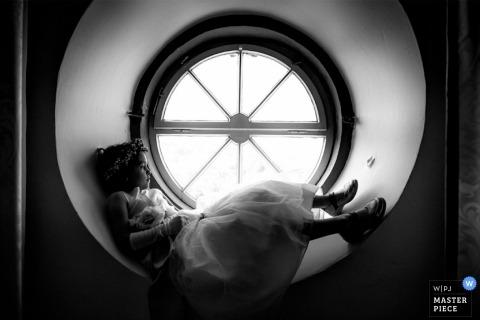 Rheinland-Pfalz Wedding Photographer | Image contains: little girl dress sitting round window