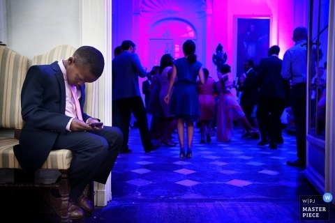 Turin Wedding Photographer | Image contains: boy phone games dancing guests blue pink lights reception