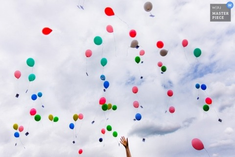 Baden-Wurttemberg  Wedding Photographer | Image contains: balloons released clouds sky hand reception