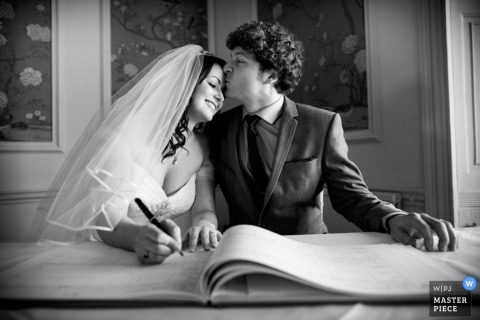 England Wedding Reportage Photography   Image contains: bride signing marriage certificate groom kissing head