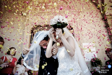 Pescara Wedding Photographer   Image contains: flower petals shower ceremony bride groom church red yellow