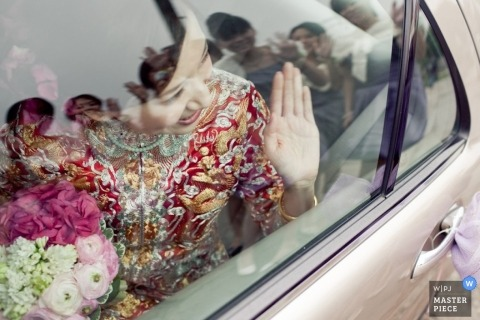 Hong Kong Documentary Wedding Photographer   Image contains: bride car limo wave flowers reflection family happy