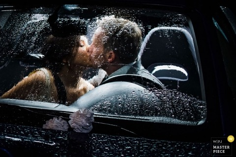 Seattle Portrait Wedding Photographer | Image contains: bride groom kissing inside car rain glass