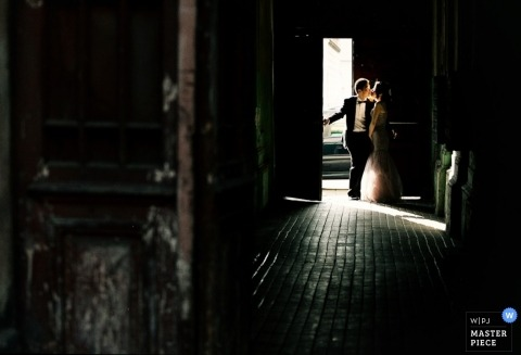 Bytom Wedding Photographer | Image contains: bride groom kissing door light natural dress tux