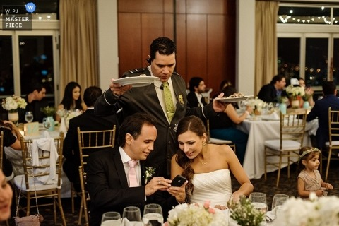Scotland wedding photographer captured this photo of the bride and groom looking at an image on his phone while entrees are being served at the reception
