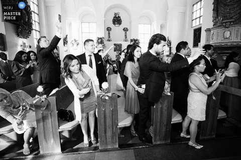 A wedding photographer captured this black and white photo of a crowd full of wedding guests holding out their phones to capture their own images of the special moment