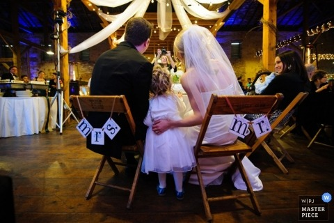 A wedding photographer captured this photo of the bride and groom sitting in mislabeled chairs at the wedding reception
