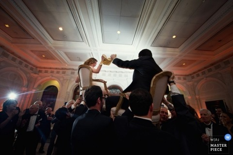 Denver wedding photographer captured this photo of the bride and groom toasting as they are hoisted in chairs above the dance floor