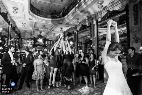 A wedding photographer captured this black and white photo of the bride throwing her bouquet into a crowd of eager guests