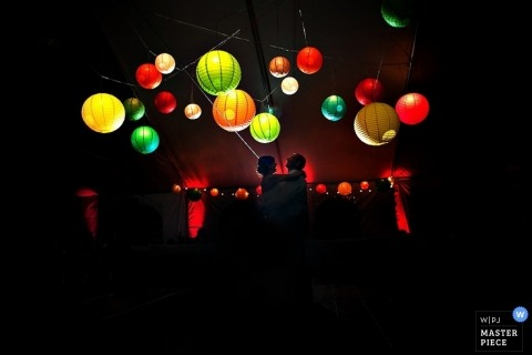 Jacksonville wedding photographer captured this photo of the bride and groom dancing in the glow of multi colored paper lanterns
