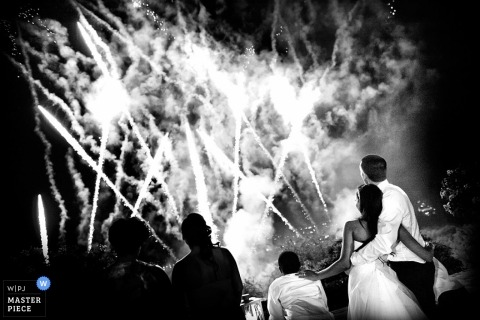 Arezzo wedding photographer created this black and white photo of the bride and groom watching fireworks after their ceremony