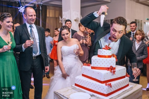Brussels wedding photographers - Belgium humorous photo of the groom pretending to stab the wedding cake while the bride stands nearby, looking concerned