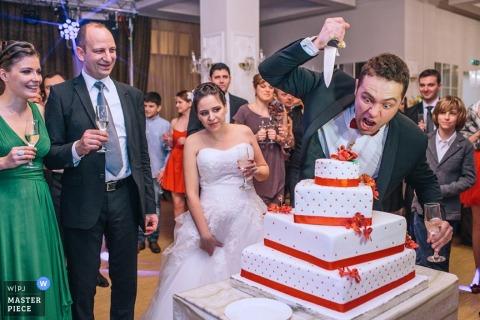 Brukselscy fotografowie ślubni - Belgia humorystyczne zdjęcie pana młodego udającego nożem tort weselny, podczas gdy panna młoda stoi w pobliżu, wyglądając na zaniepokojoną