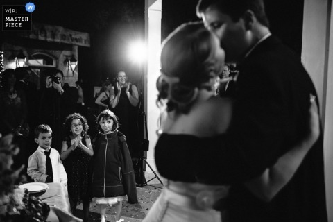 San Antonio wedding photographer captured this black and white photo of the bride and groom kissing while young wedding guests looked on.