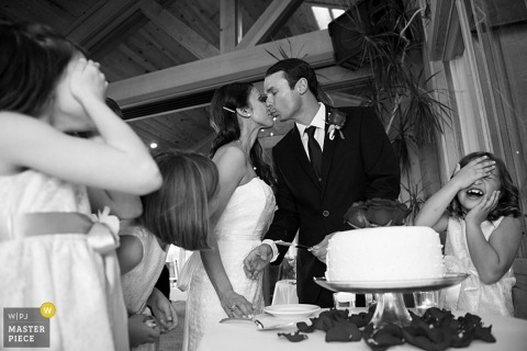 Lake Tahoe wedding photographer captured this black and white photo of the bride and groom kissing in front of their cake