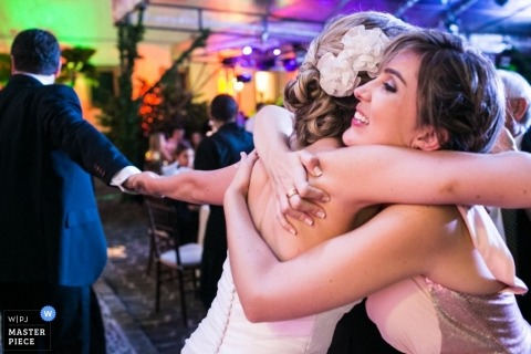 Bahia wedding photographer captured this bride giving a bridesmaid a hug as her groom tries to pull her to the dancefloor