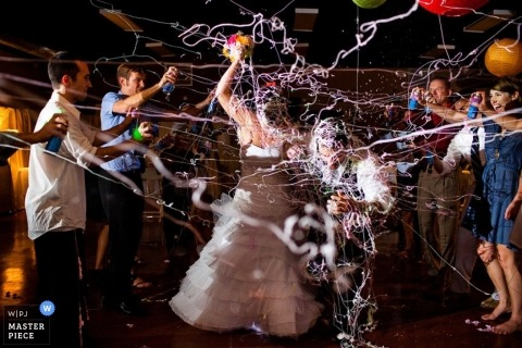 A wedding photographer captured this photo of the bride getting showered with silly string at their reception