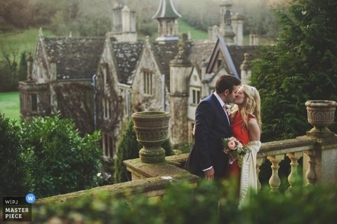 A wedding photographer -  beautiful portrait of a couple kissing in front of a large stone castle