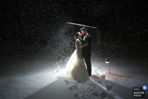 New Jersey wedding photographer captured this image of the bride and groom kissing under an umbrella in a snowstorm