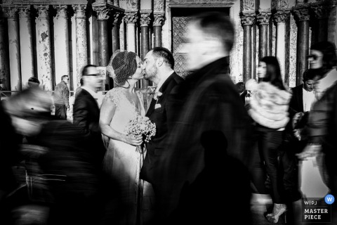 Venice wedding photography of the bride and groom kissing while guests walk around in the background