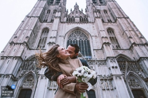 Brussels wedding photographer created this photo of the bride and groom embracing in front of the church as she holds her bouqet
