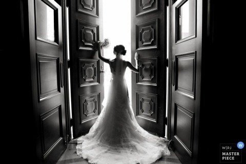 Knoxville wedding photographer captured this black and white photo of the bride standing in front of a large open doorway holding her bouquet
