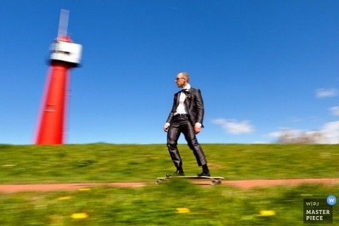 Zuid Holland wedding photographer captured this photo of the groom skateboarding down a path in a meadow