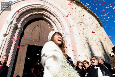 Wedding photographer captured this photo of a smiling bride being showered in confetti outside of a church