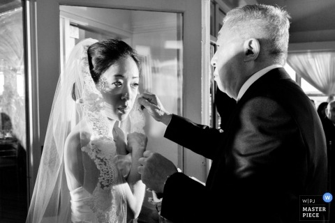 San Francisco wedding photographer captured this black and white photo of the brides father carefully wiping a tear from her cheek