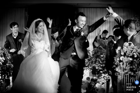 Tianjin wedding photographer captured this black and white photo of the groom high fiving wedding guests as he walks down the aisle after the ceremony