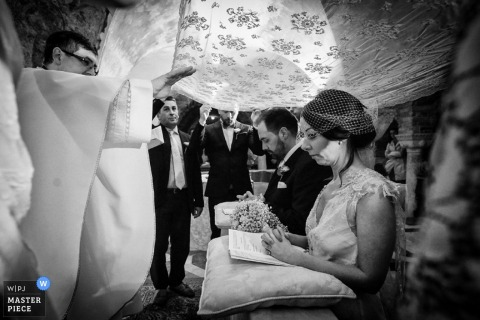 Venice wedding photography - Photo of the bride and groom being blessed during their ceremony