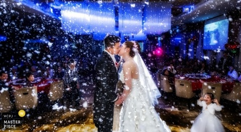 Hong Kong wedding photographer captured this photo of the bride and groom kissing on the dance floor under a shower of confetti