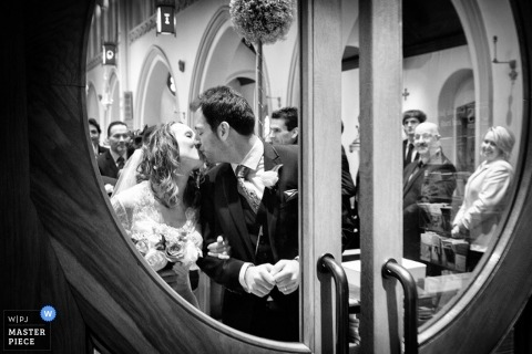Leicestershire wedding photographer captured this black and white photo through a glass window of the bride and groom kissing after their ceremony