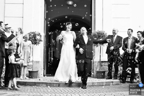 Vienna wedding photographer captured this black and white photo of bride and groom walking out of the church into a shower of bubbles