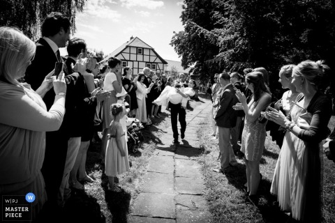 Lower Saxony wedding photographer captured this black and white photo of a groom carrying his bride down a path lined with guests