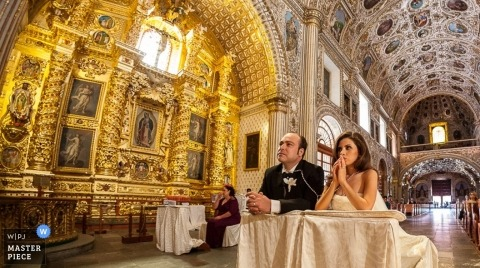 A wedding photographer captured this photo of the bride and groom kneeling during their ceremony in the church