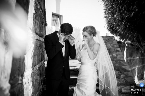 San Francisco wedding photographer captured this black and white photo of a bride and groom wiping tears after getting married
