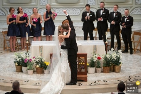 Chicago wedding photographer | Image of the bride and groom kissing at their ceremony, as the groom fist pumps the air