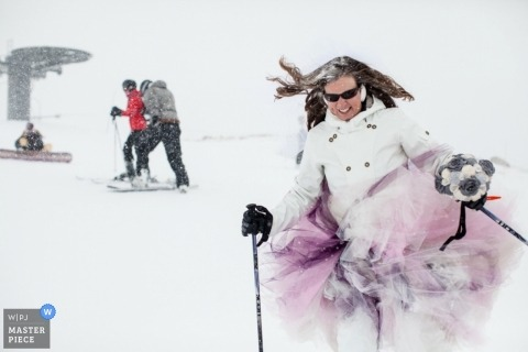 Montana wedding photographer captured this photo of the bridesmaid skiing in the snow with her dress on and holding her bouquet