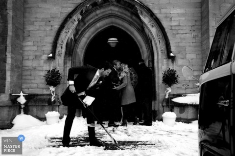 A wedding photographer captured this black and white photo of a wedding guest shoveling snow off the church walk way