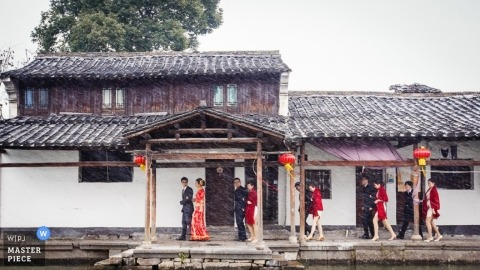 Hangzhou city wedding photographer - photo of the bridal party taking shelter under an awning during a rain storm